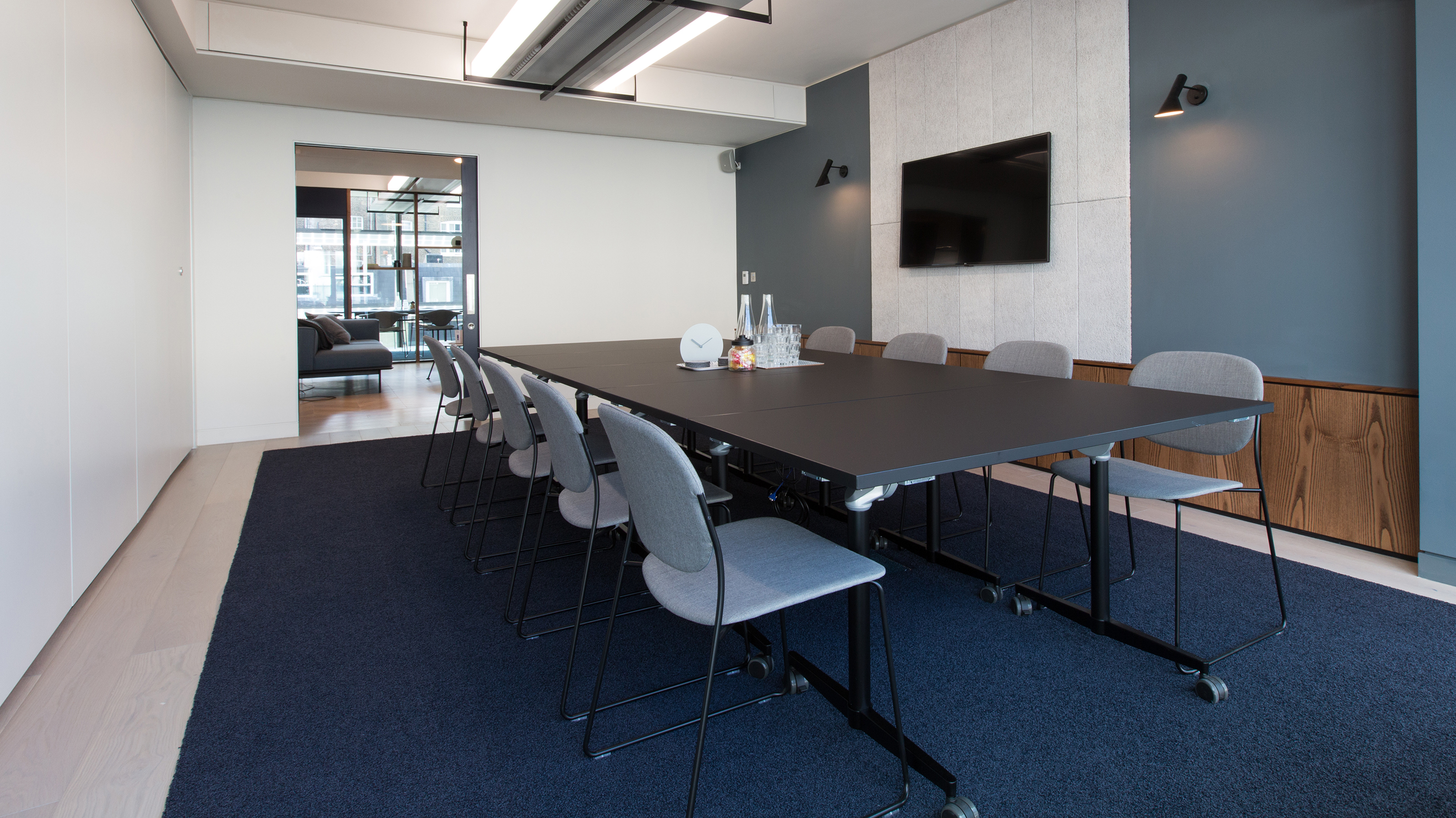 Medium meeting room with black rectangular table and grey chairs and tv screen at TOG building 20 Eastbourne Terrace London