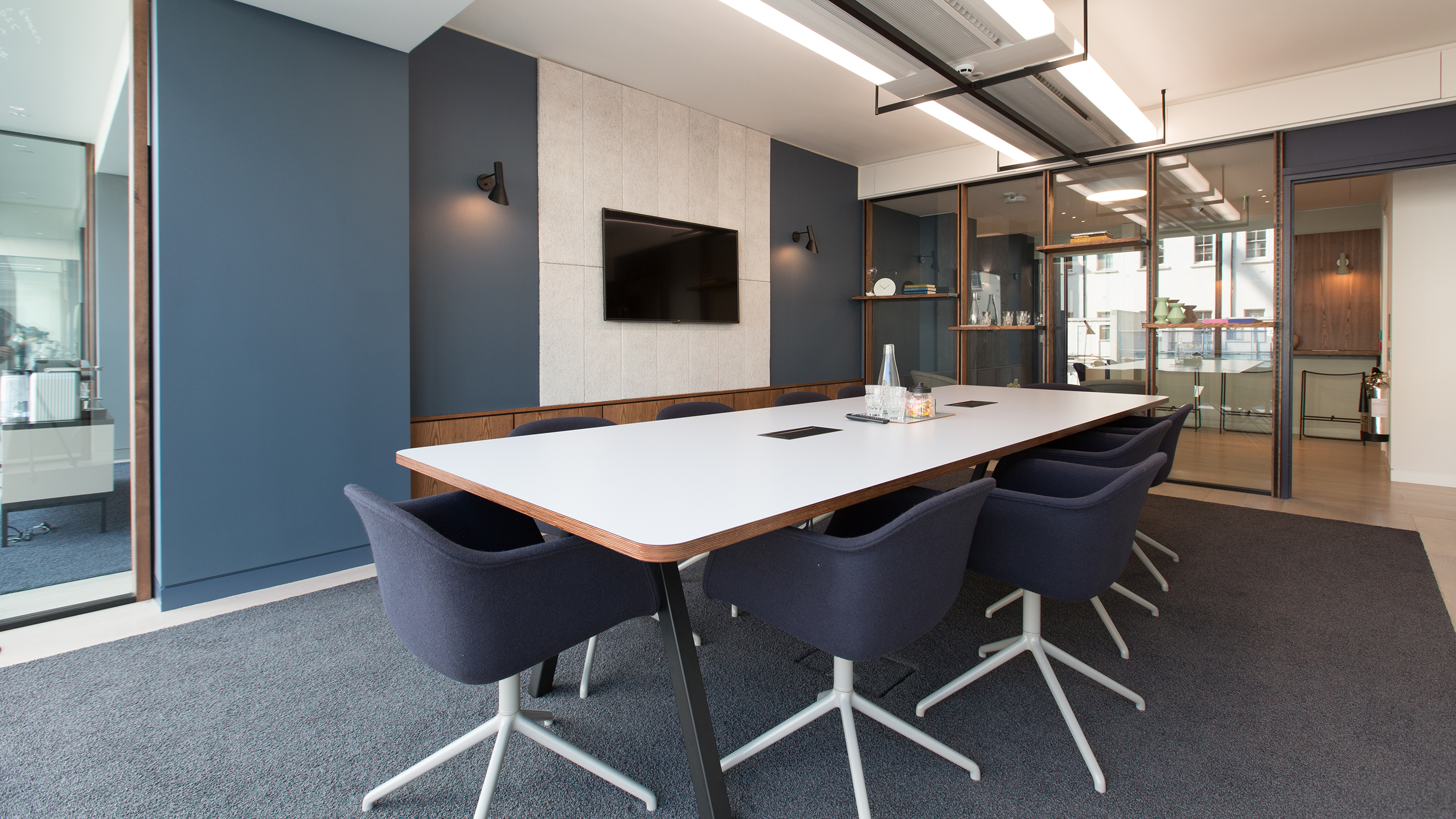 Medium meeting room with white rectangular table and navy chairs and tv screen at TOG building 20 Eastbourne Terrace London