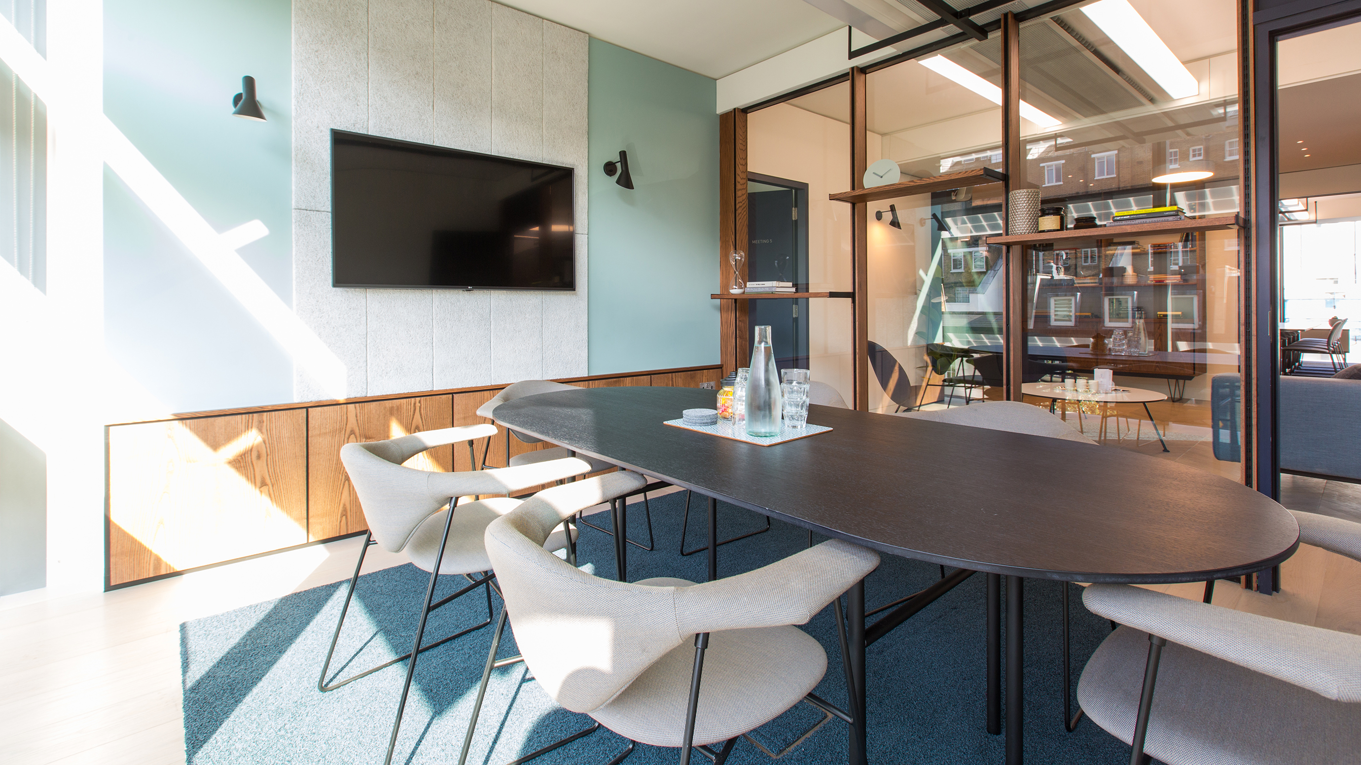 Small meeting room with oval wooden table and pale chairs and tv screen at TOG building 20 Eastbourne Terrace London