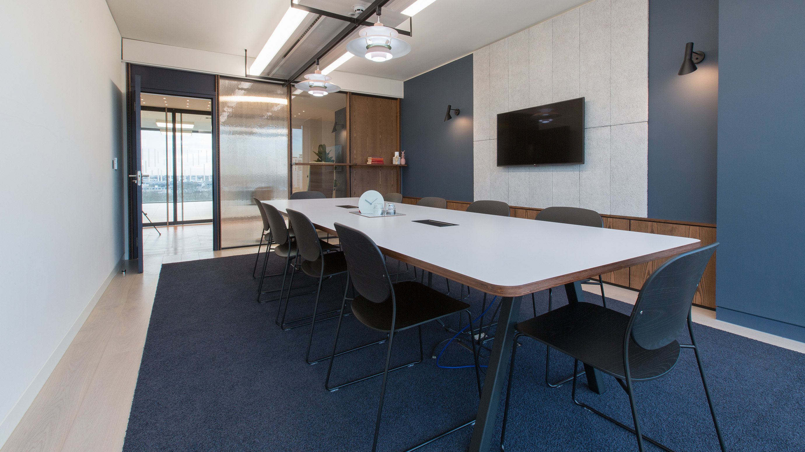 Medium meeting room with white rectangular table and black chairs and tv screen at TOG building 20 Eastbourne Terrace London