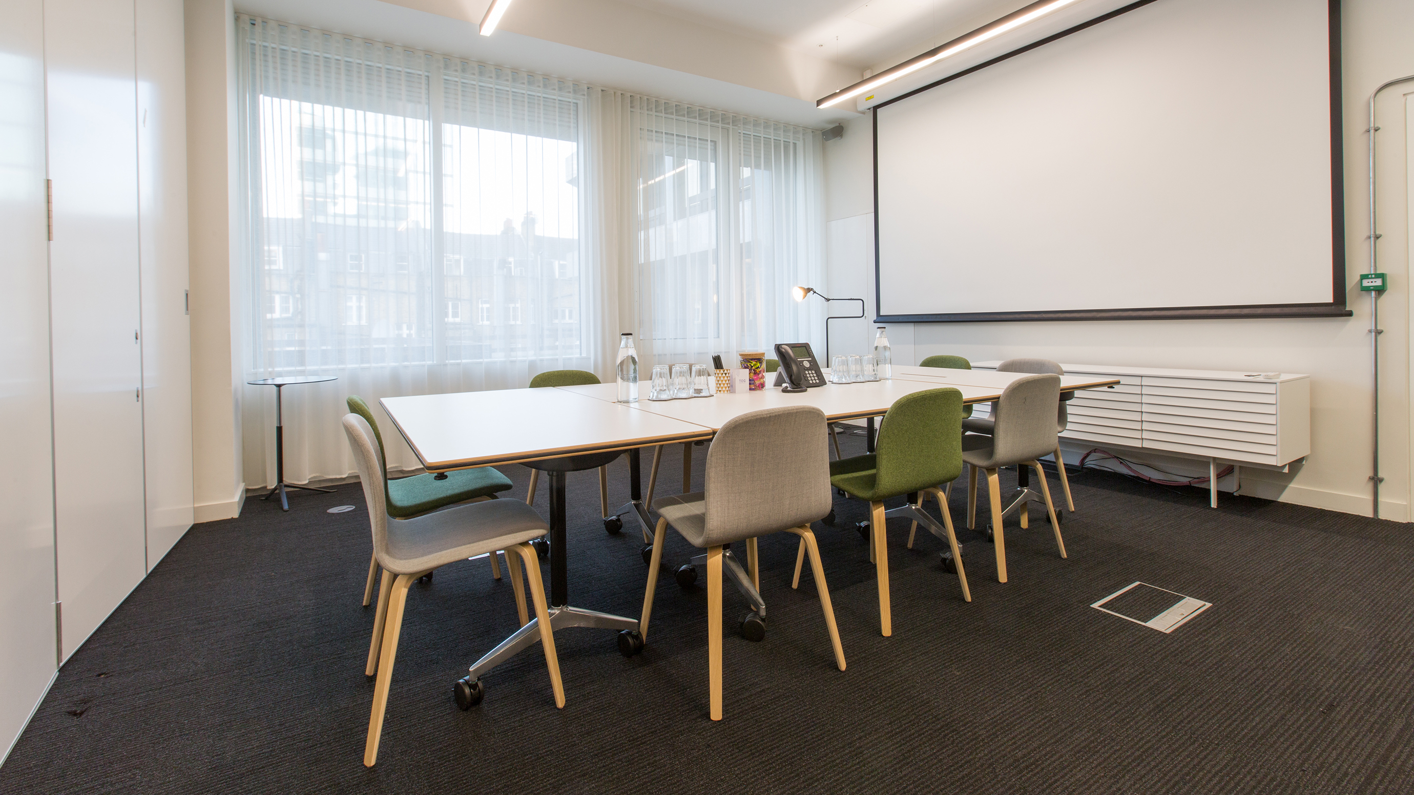 Medium meeting room with white table and grey and green chairs and screen at TOG building 2 Stephen Street London