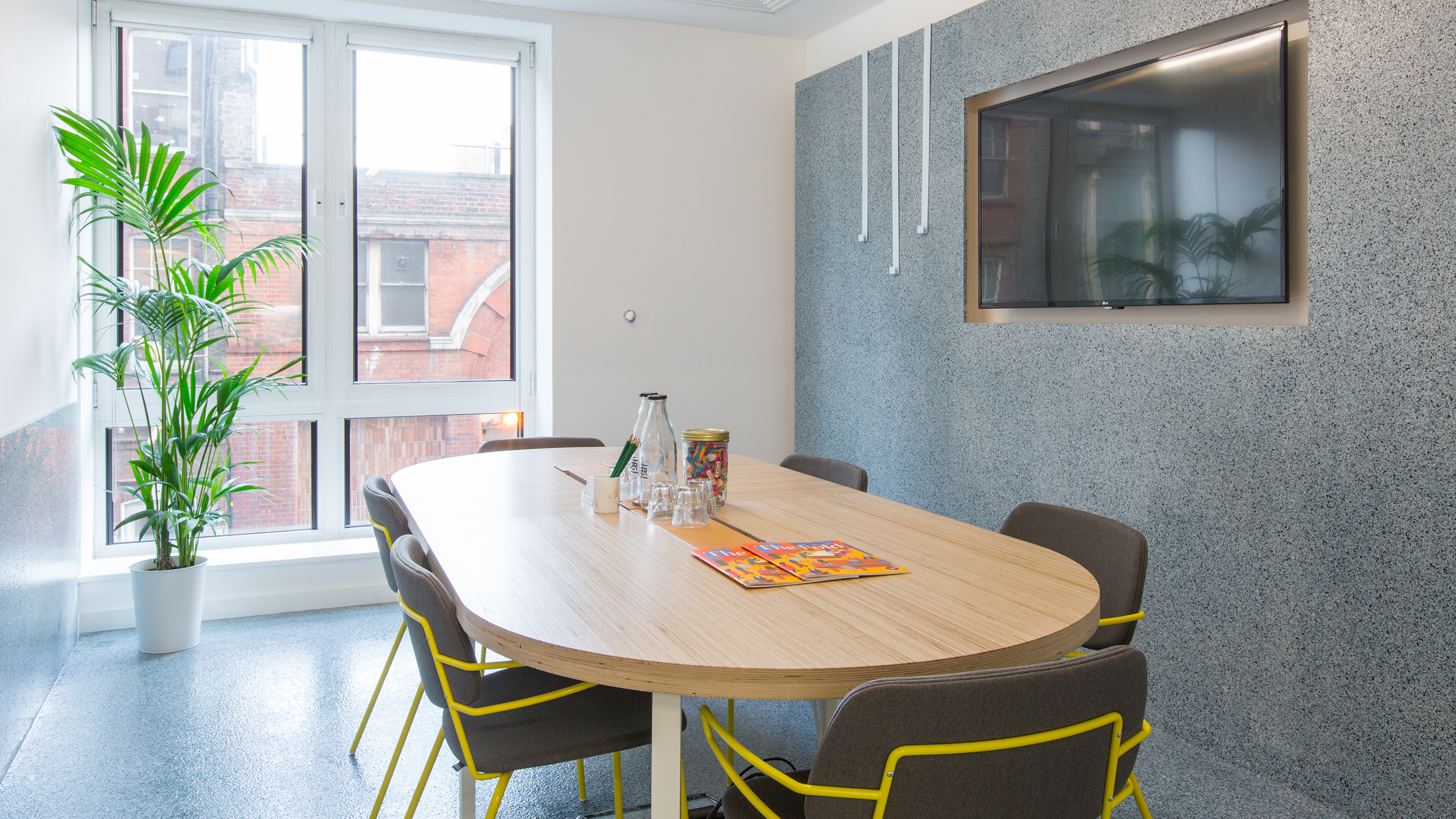 Small meeting room with wooden table and grey and yellow chairs and tv screen at TOG building 2 Angel Square London