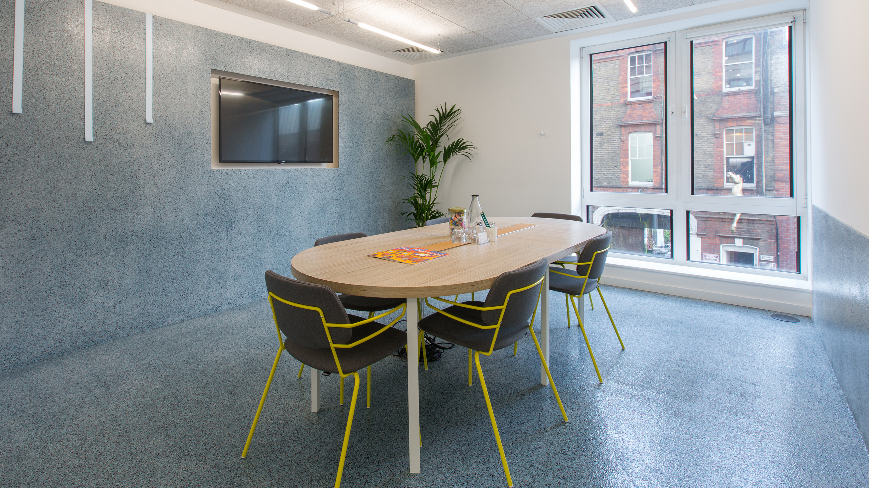 Small meeting room with wooden table and grey and yellow chairs at TOG building 2 Angel Square London