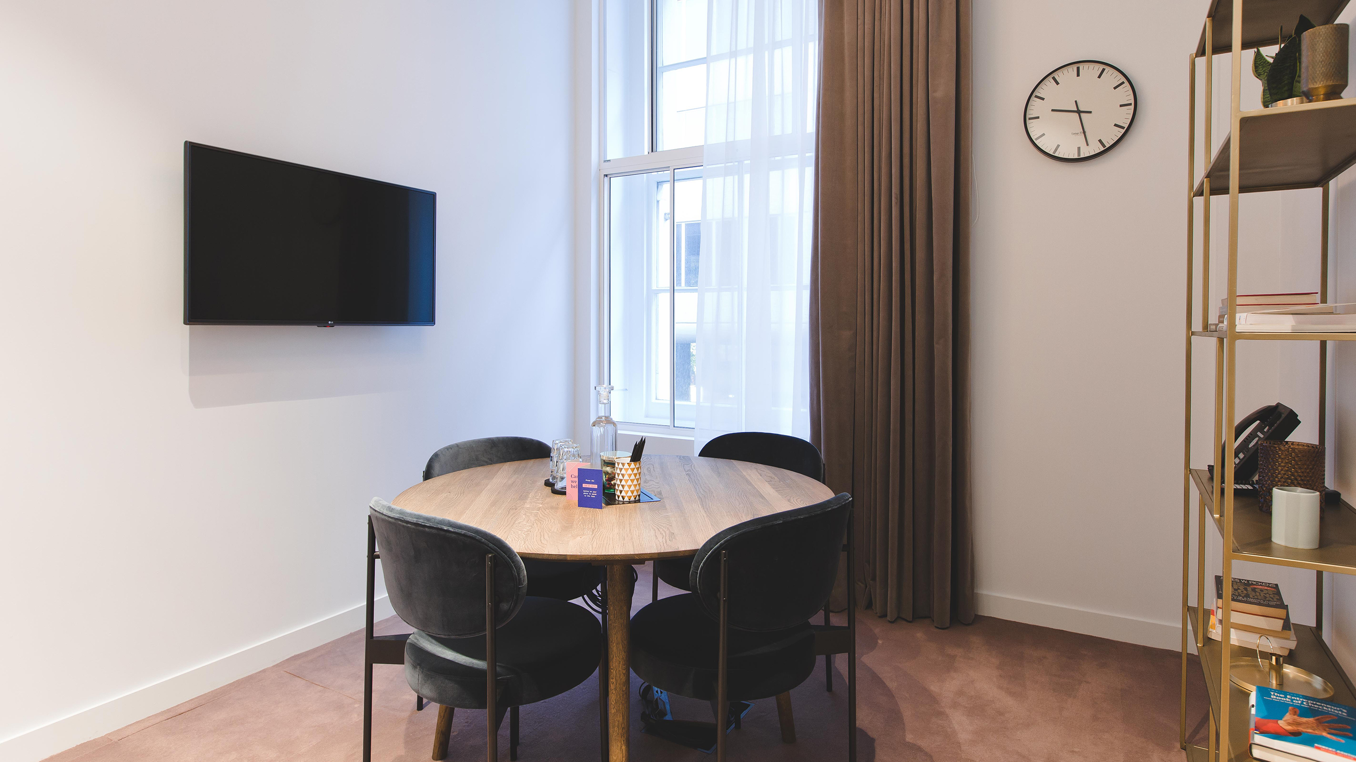 Small meeting room with brown wooden round table and black chairs and tv screen and shelves at TOG building Belle House London