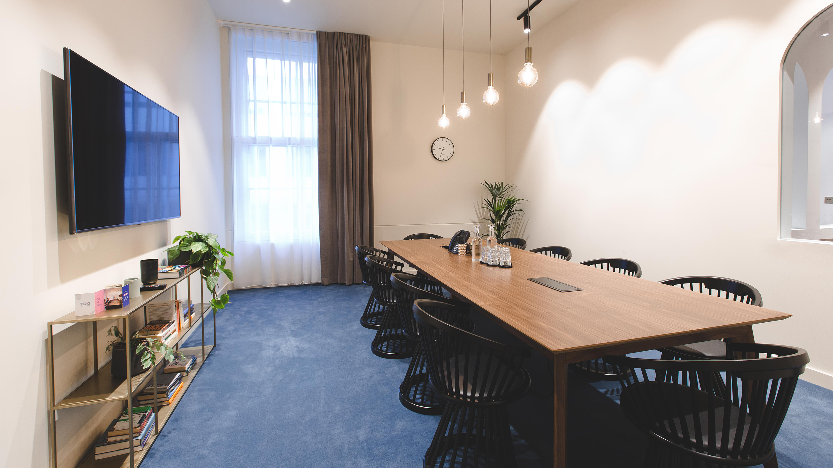 Medium meeting room with brown wooden table black chairs tv screen and shelves at TOG building Belle House London