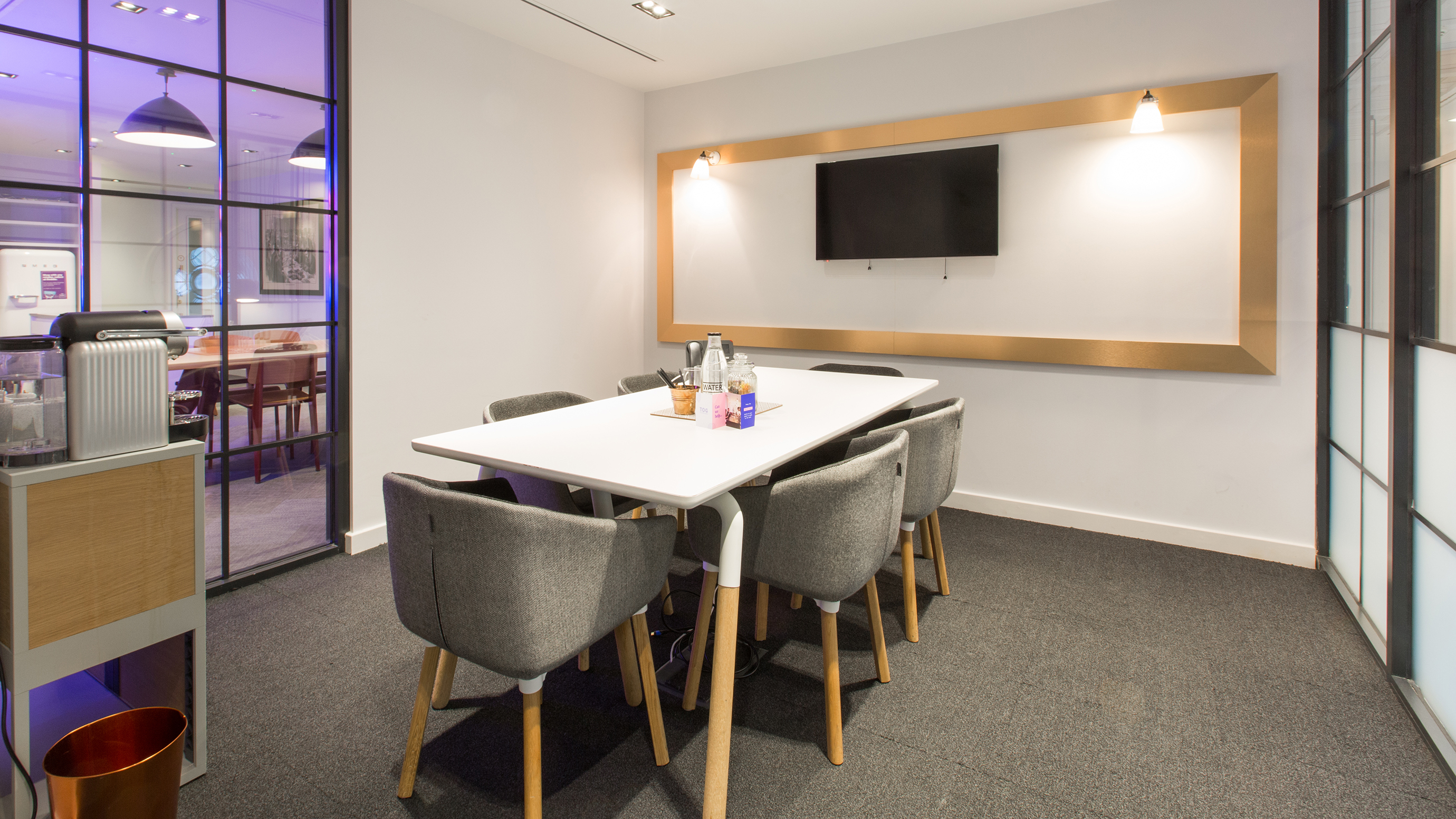 Small meeting room with white rectangular table and grey chairs and tv screen at TOG building 50 Liverpool Street London