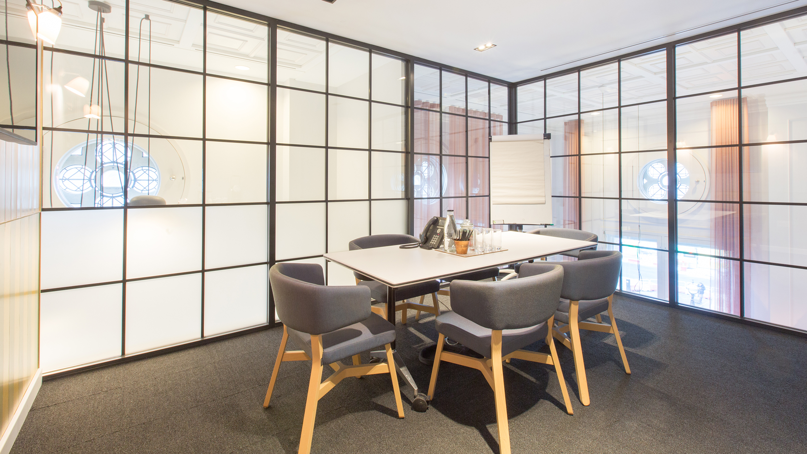 Small meeting room with white rectangular table and grey chairs at TOG building 50 Liverpool Street London