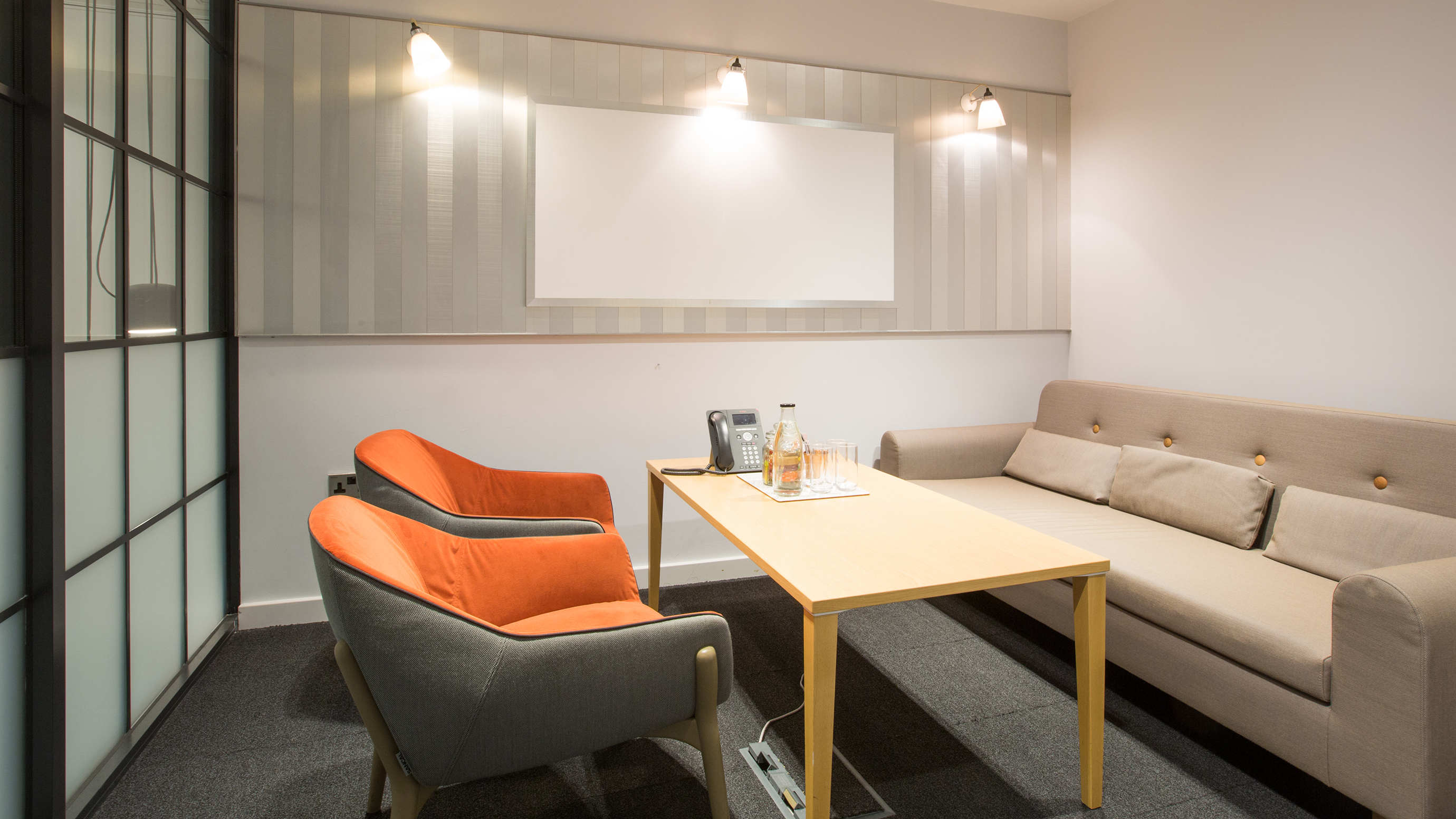 Small meeting room with wooden table sofa and orange chairs at TOG building 50 Liverpool Street London