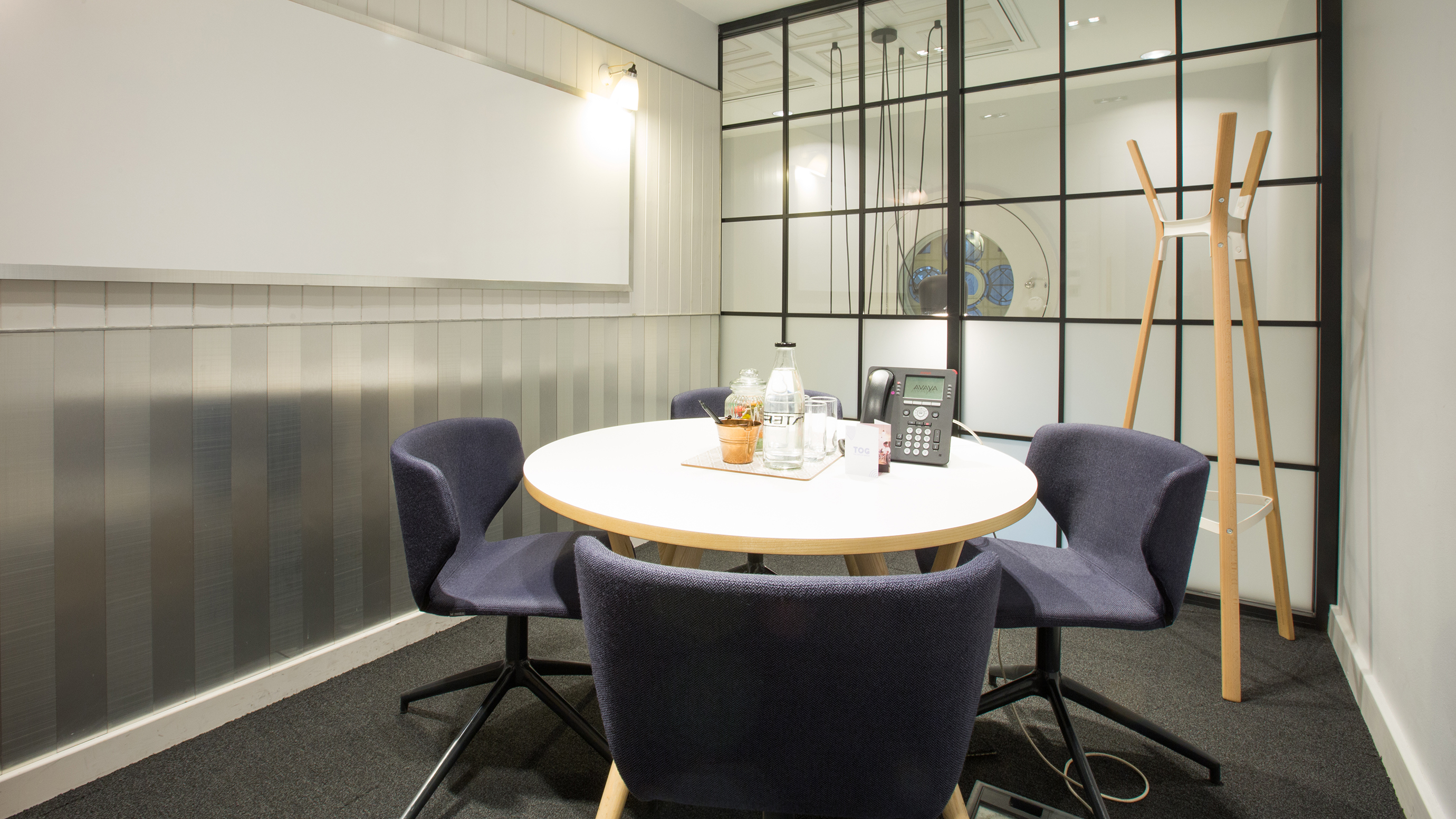 Small meeting room with white round table blue chairs and coat rack at TOG building 50 Liverpool Street London