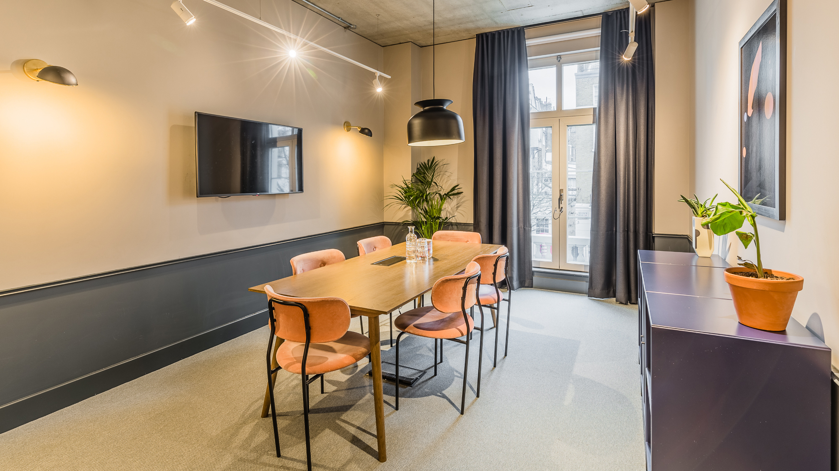 Small meeting room with wooden table and orange chairs and grey walls at TOG building Thomas House London