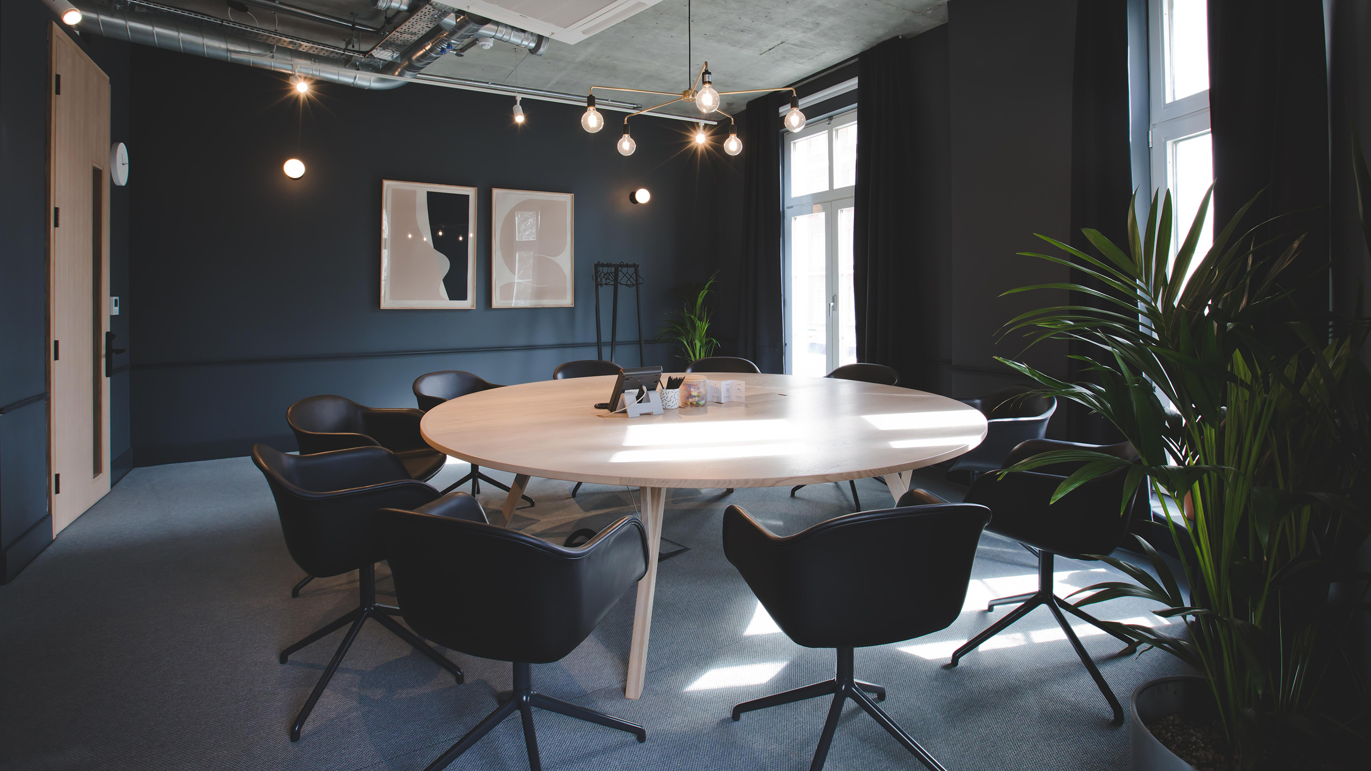 Medium meeting room with pale wooden table and dark blue chairs and wall and carpet at TOG building Thomas House London