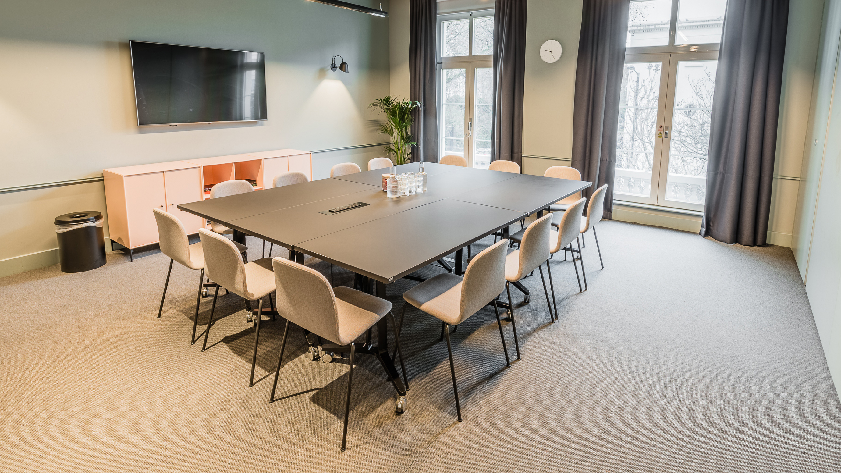 Medium meeting room with dark table and pale chairs and grey carpet and tv screen at TOG building Thomas House London