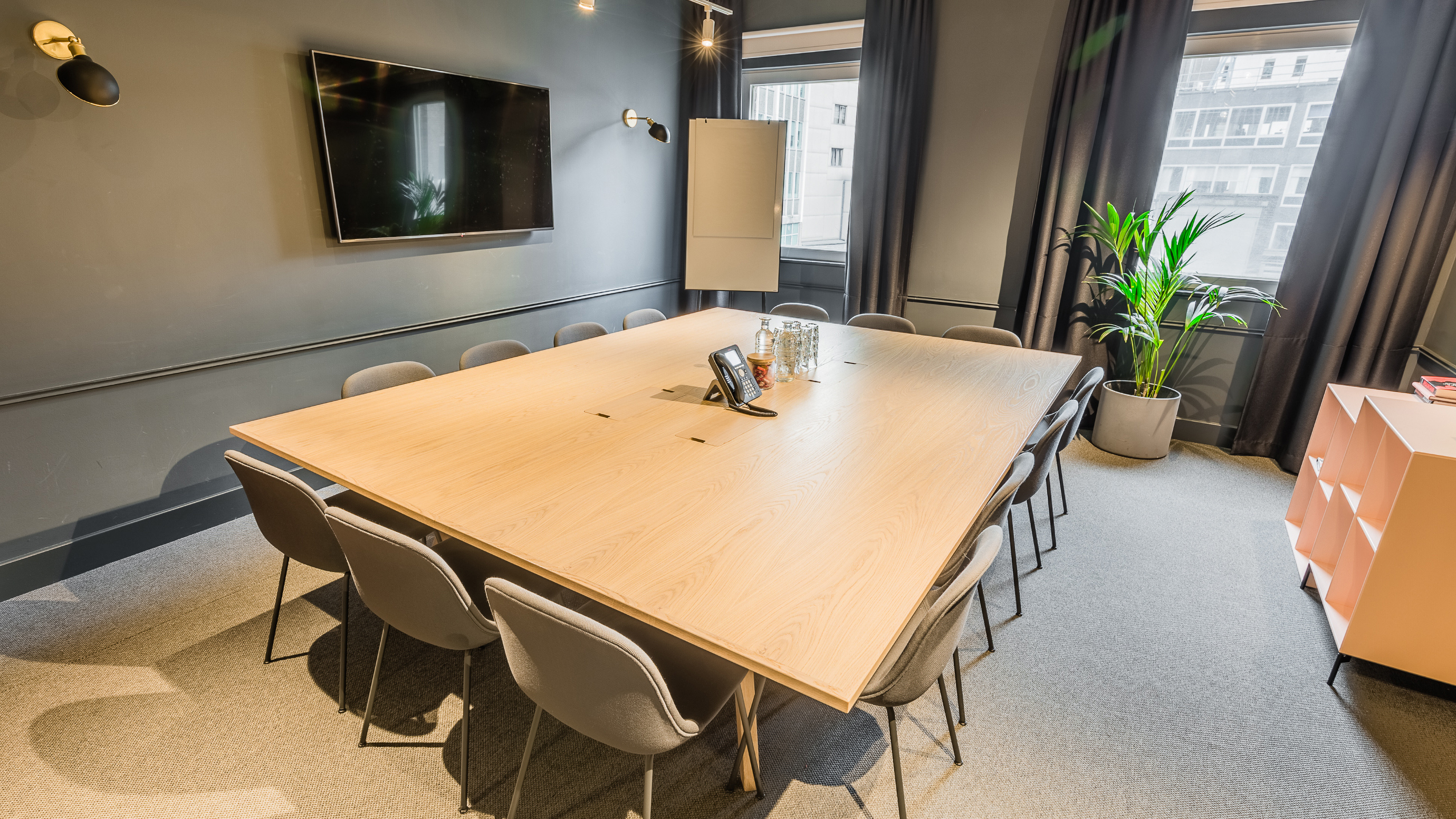 Medium meeting room with pale wooden table and grey chairs and carpet and tv screen at TOG building Thomas House London