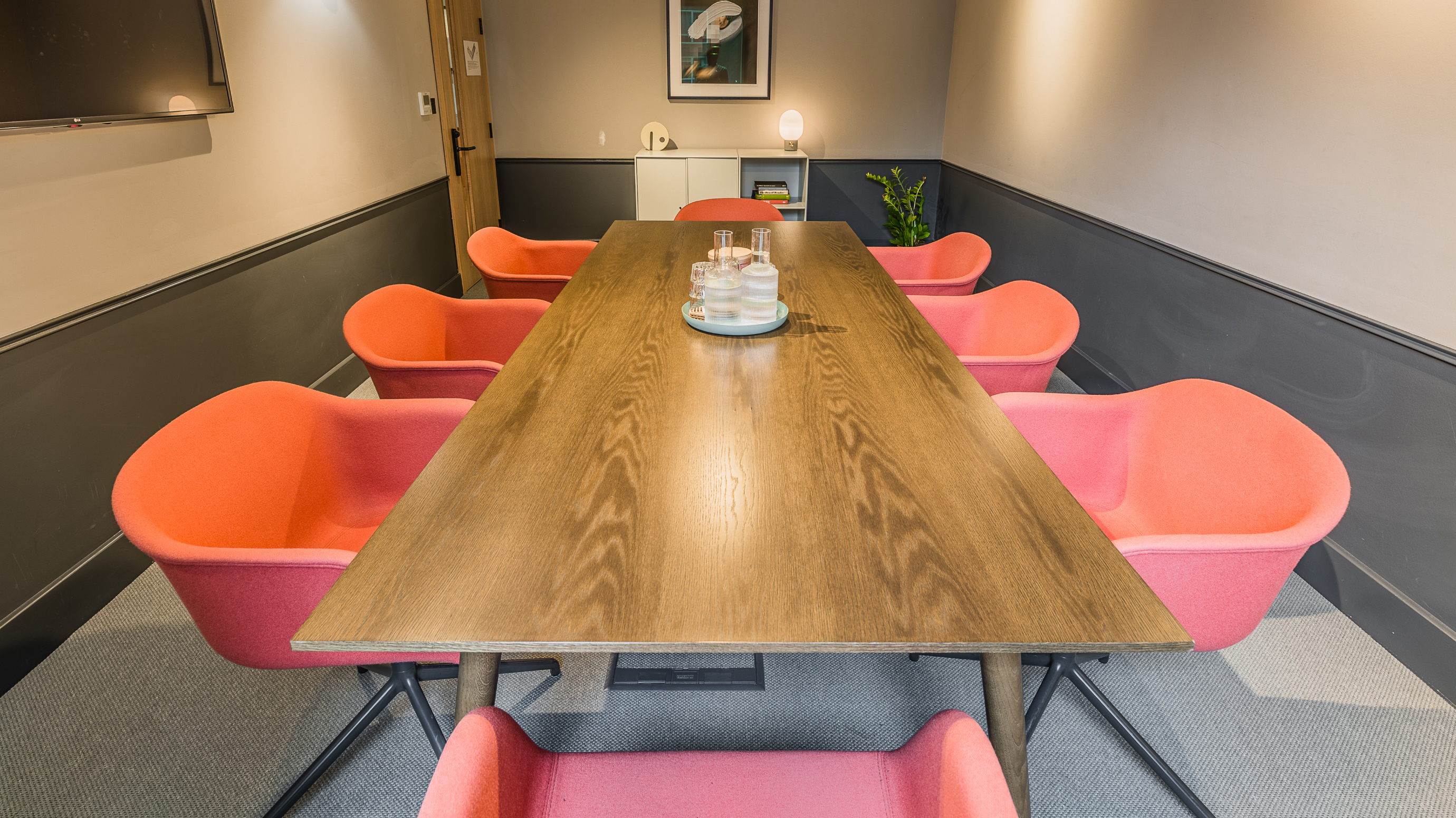 Medium meeting room with wooden rectangular table and pink chairs and grey walls at TOG building Thomas House London