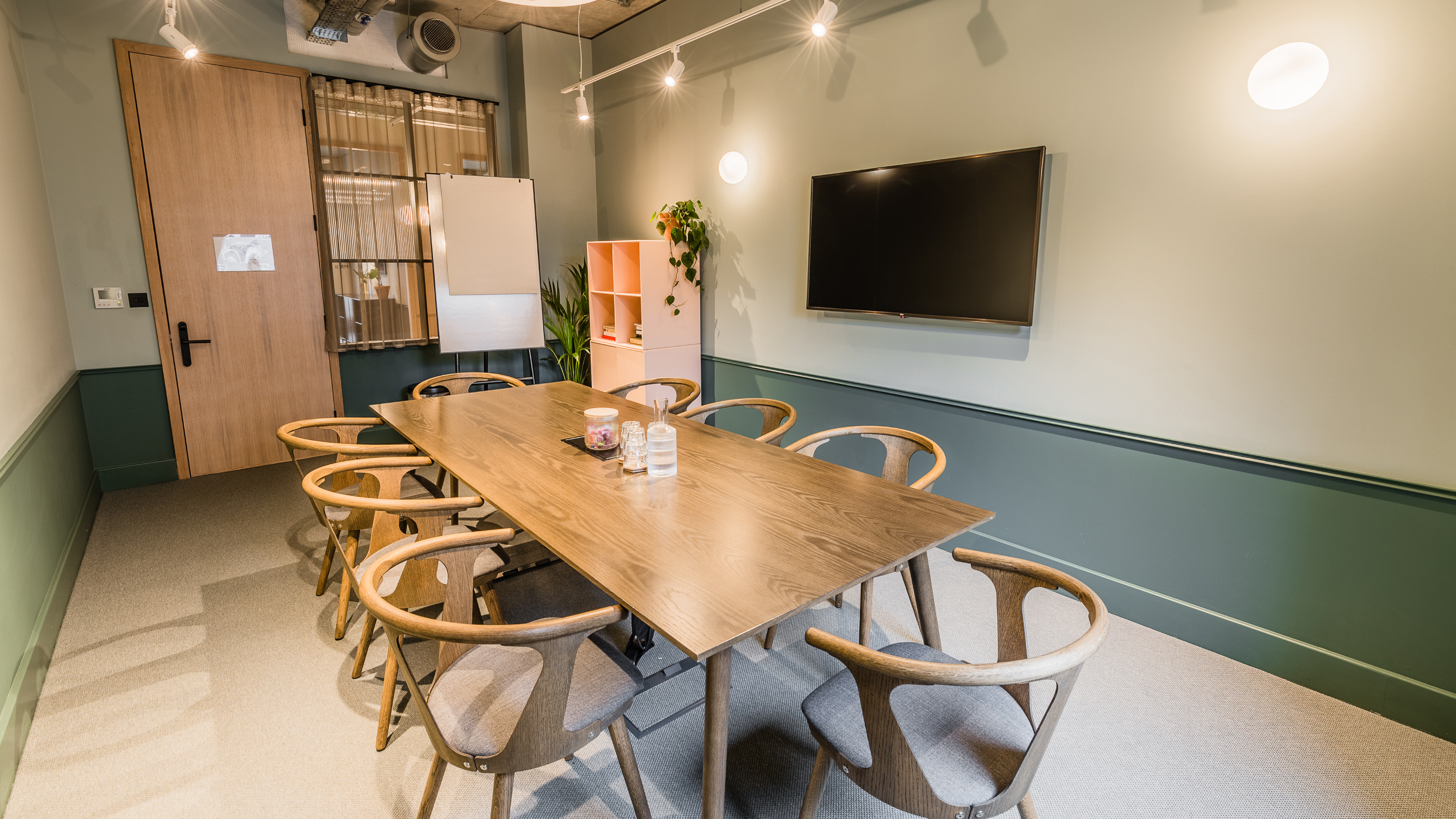 Medium meeting room with wooden rectangular table and chairs and teal walls at TOG building Thomas House London