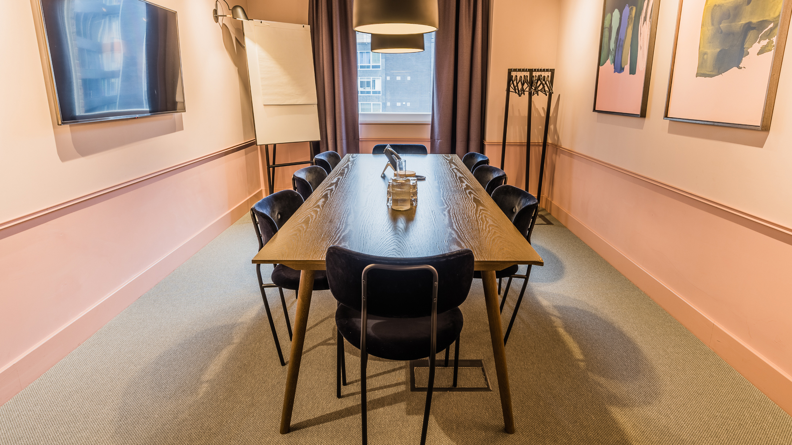Medium meeting room with wooden rectangular table and dark chairs and pink walls at TOG building Thomas House London
