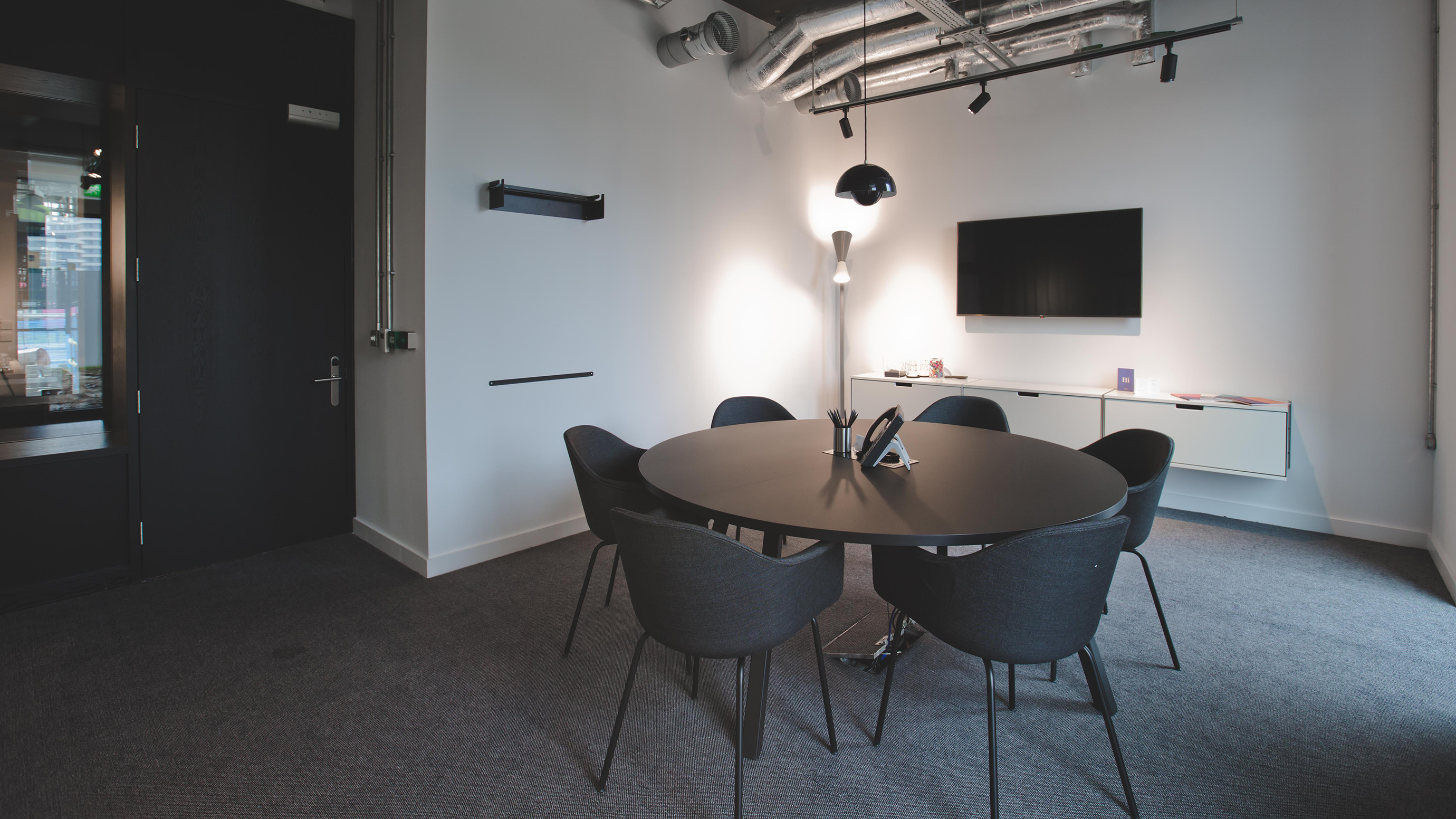 Small meeting room with round table and dark chairs and carpet at TOG building Tintagel House London