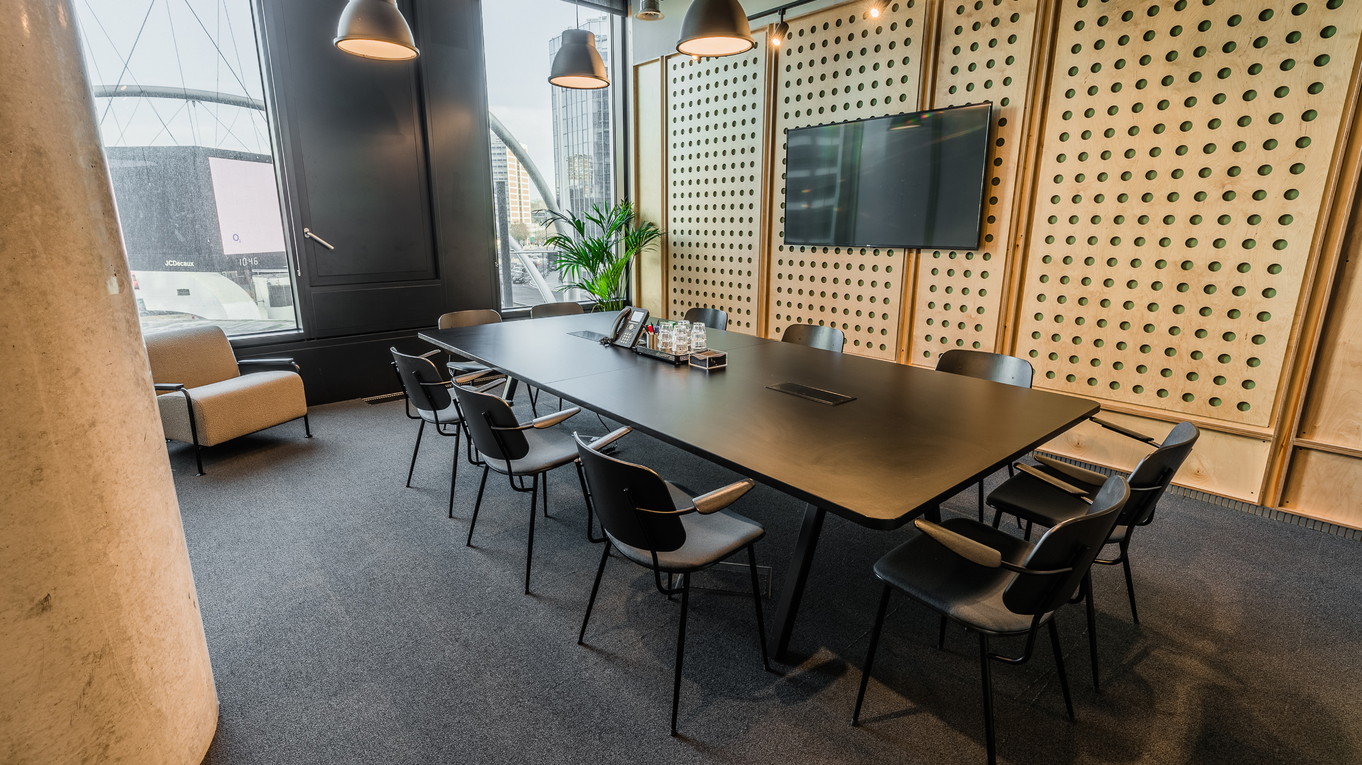 Medium meeting room with dark table and chairs and wooden panelled walls and tv screen at TOG building White Collar Factory London