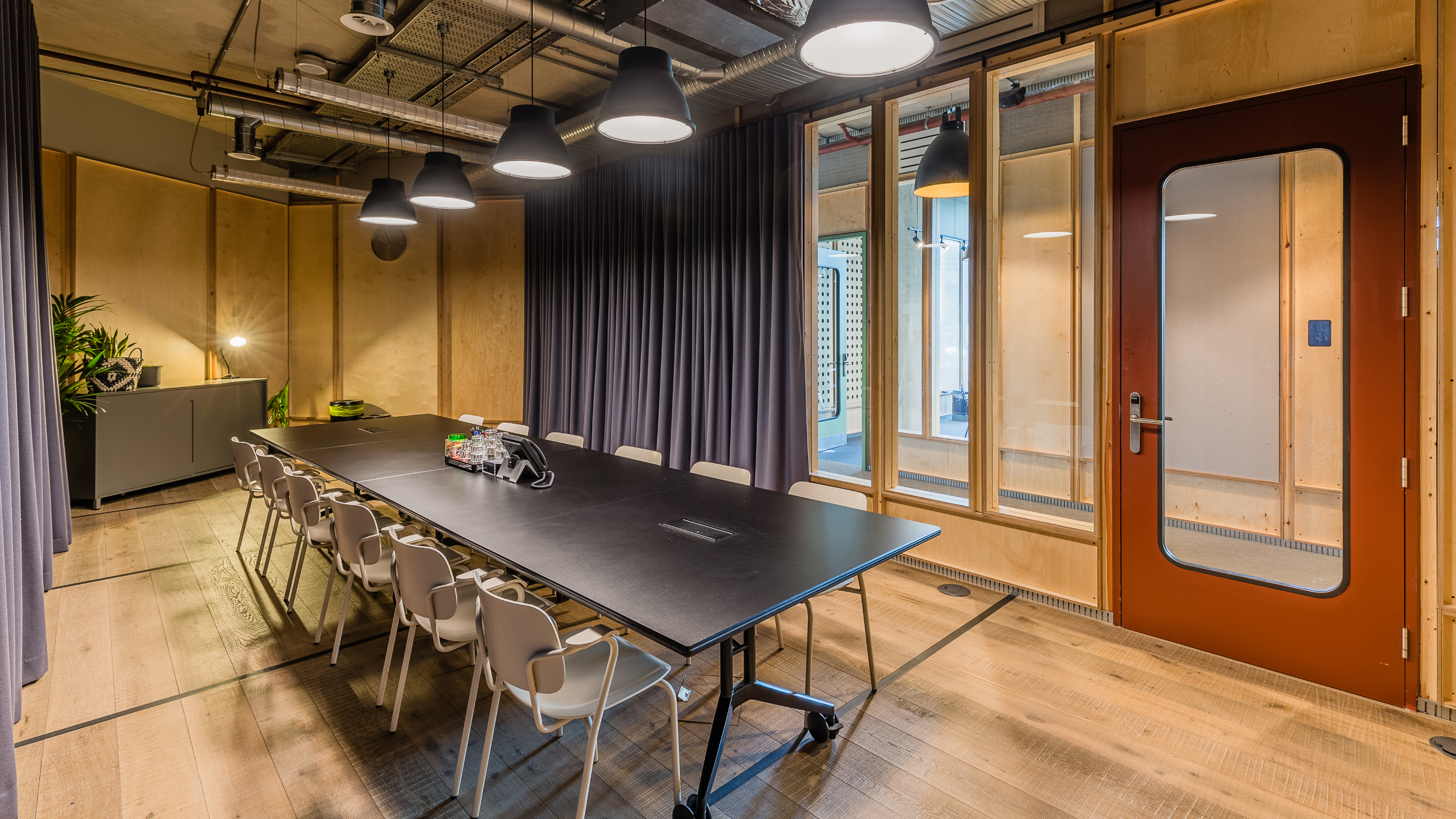 Medium meeting room with dark table and pale chairs and grey curtain and wooden floorboards at TOG building White Collar Factory London