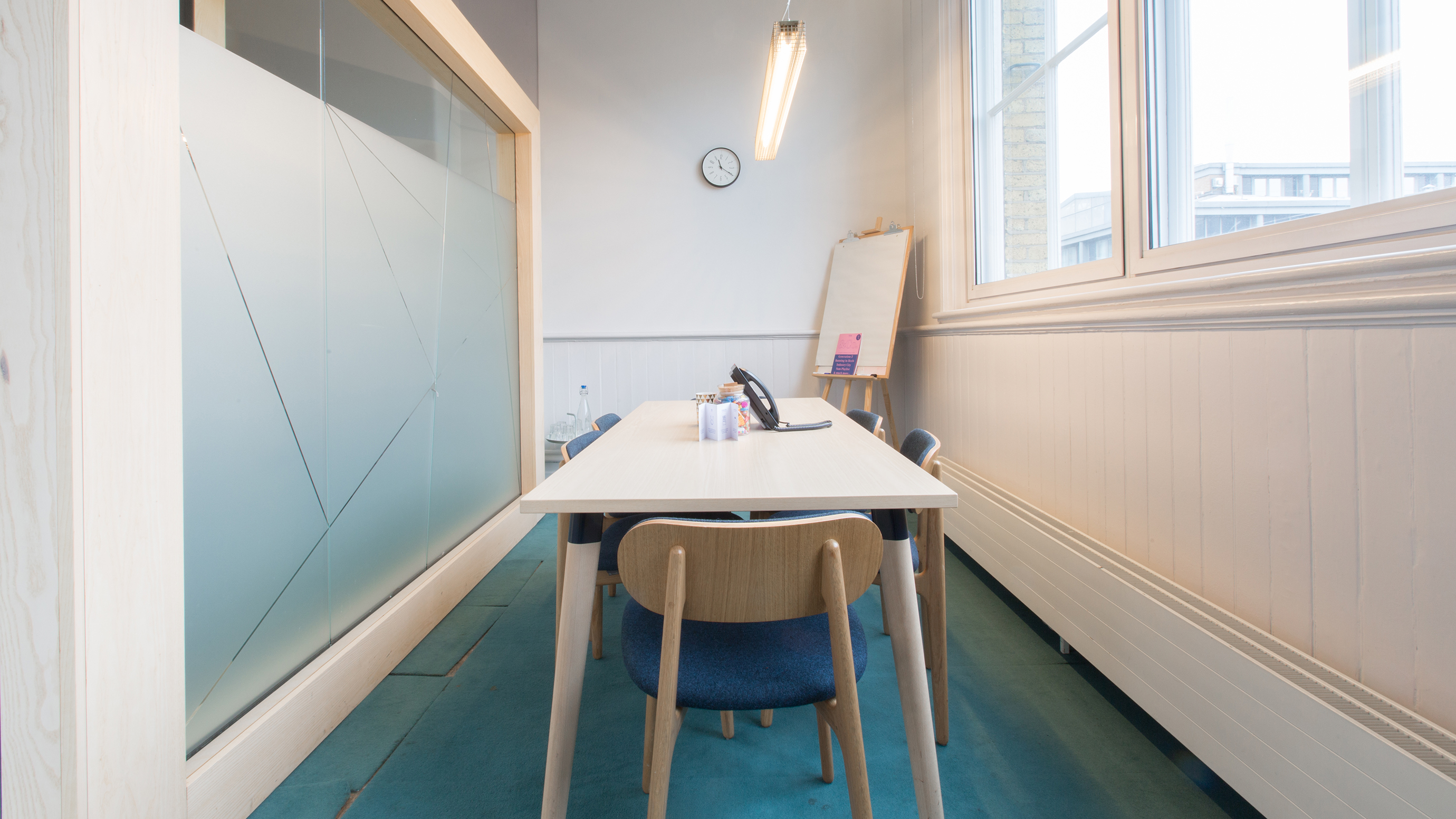 Small meeting room with pale wooden table and chairs and flipchart at TOG building East Side London