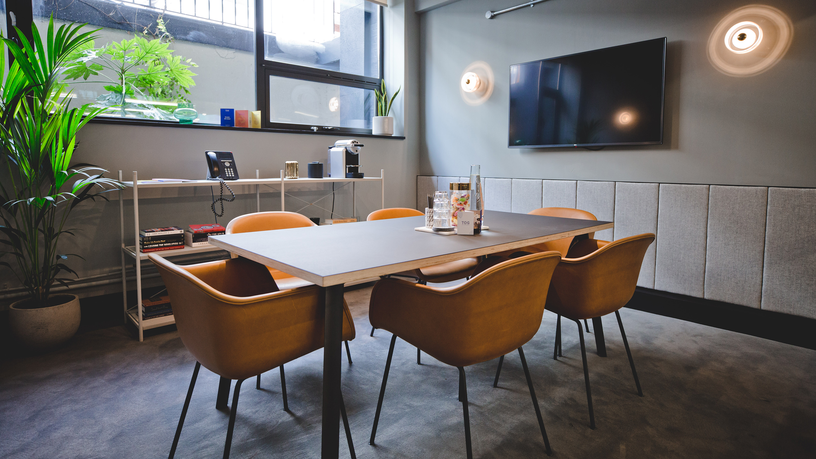 Small meeting room with rectangular table and mustard chairs and tv screen at TOG building Kirby Street London