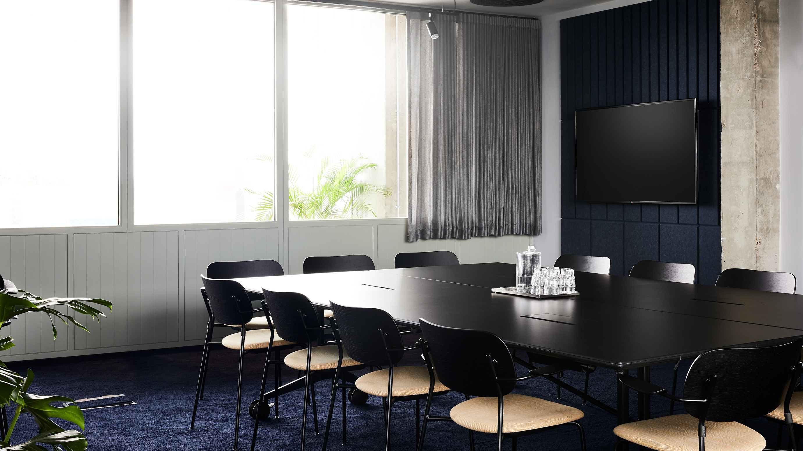 Medium meeting room with black table and wooden chairs and grey curtains at TOG building One Lyric Square London