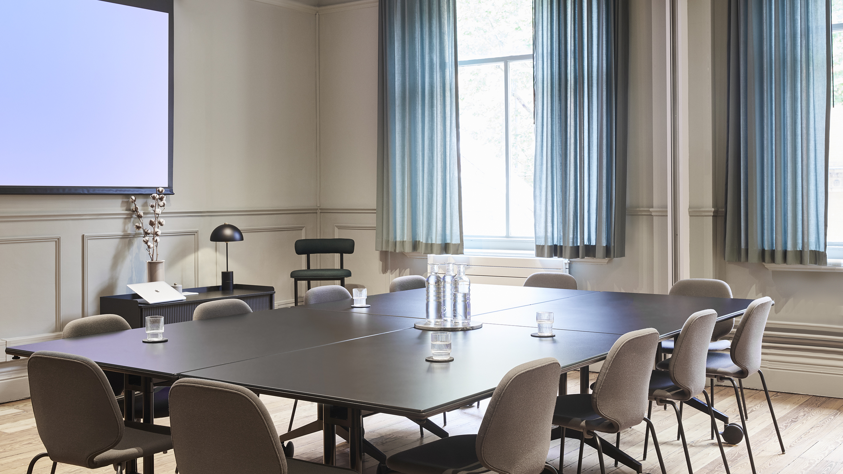 Medium meeting room with dark wooden table and grey chairs and screen at TOG building Melcombe Place London