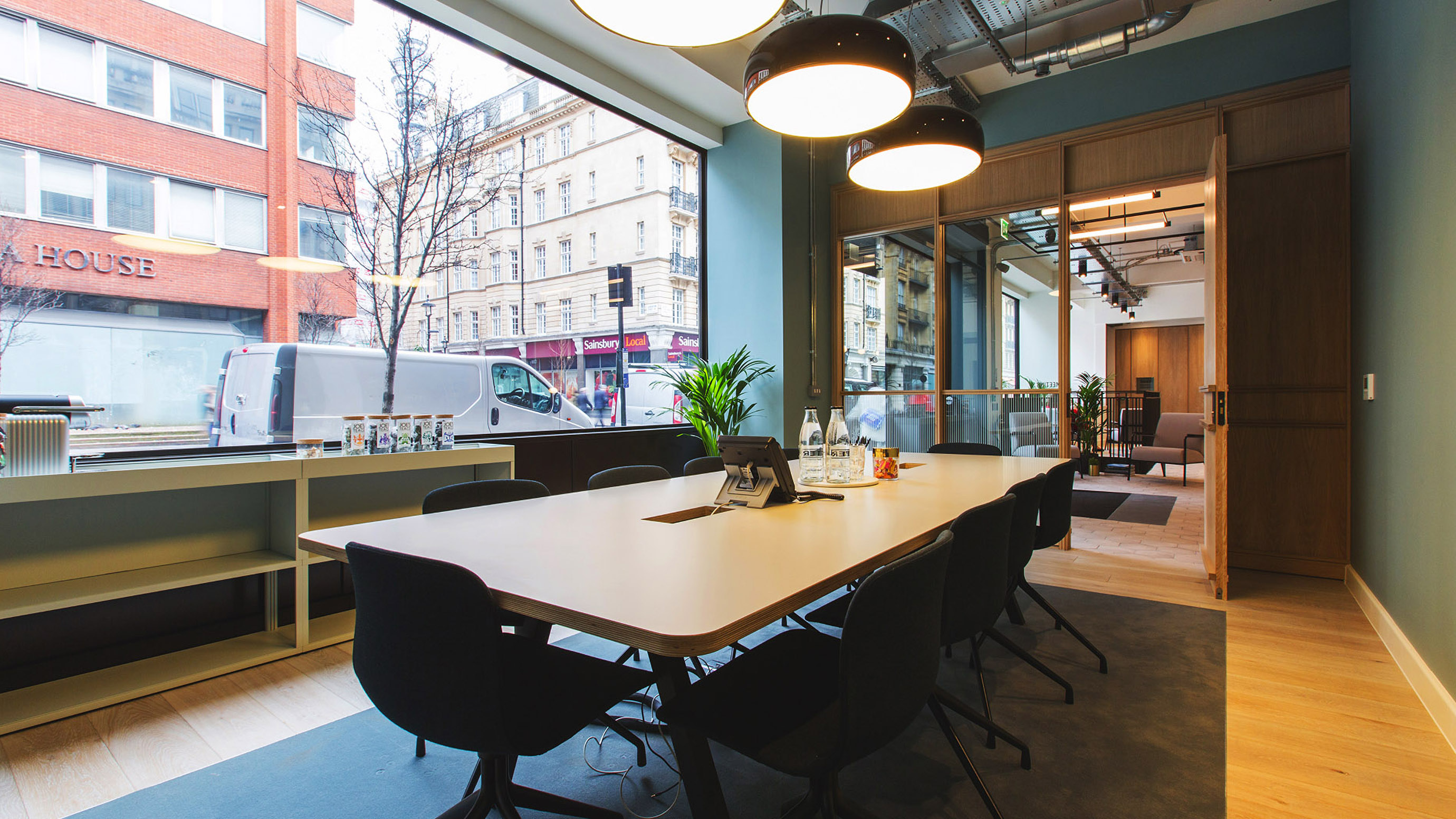 Medium meeting room with pale wooden table and dark chairs and street view at TOG building Smiths Building London