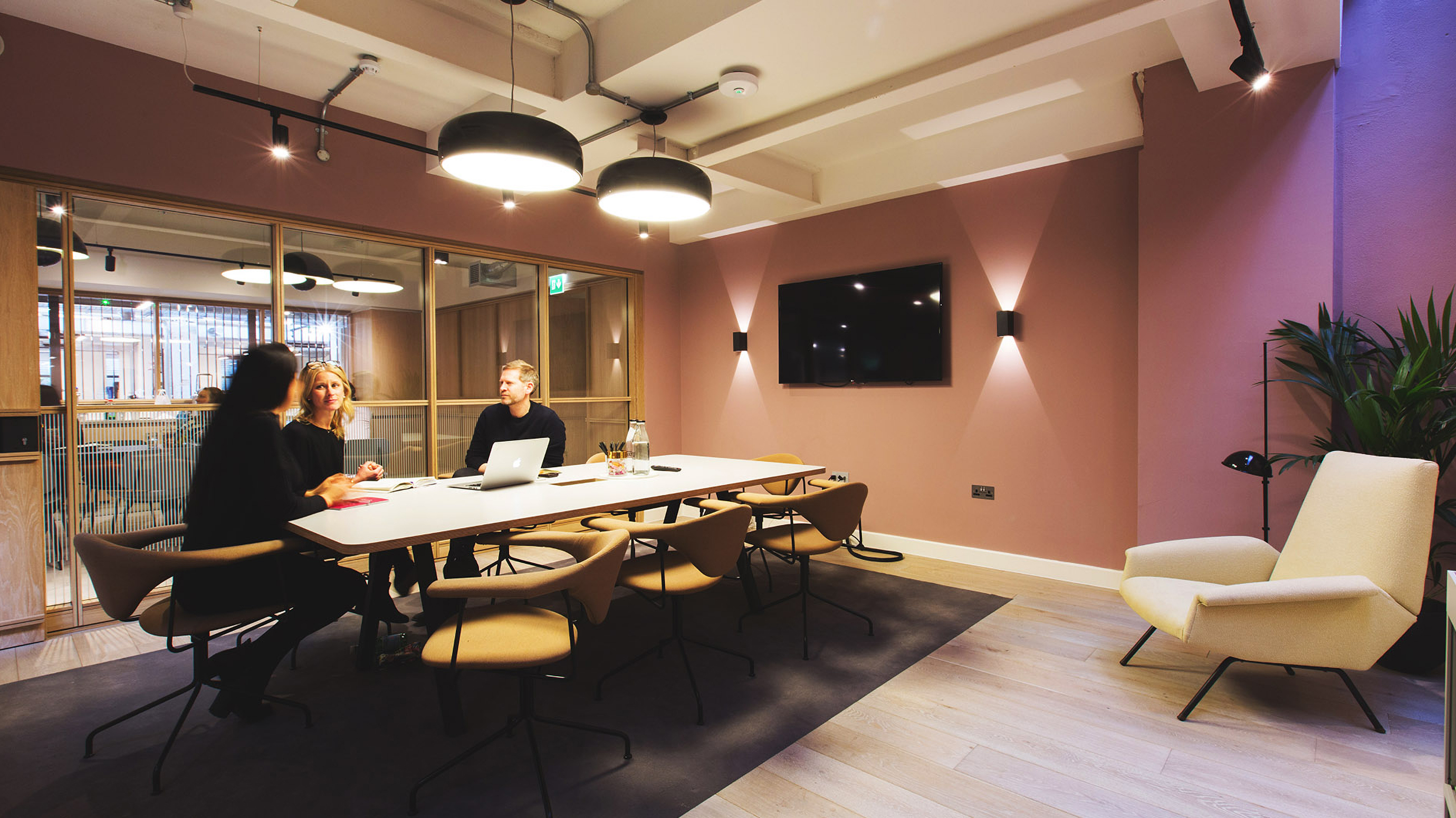 Medium meeting room with long white table and pale chairs and pink walls and tv screen at TOG building Smiths Building
