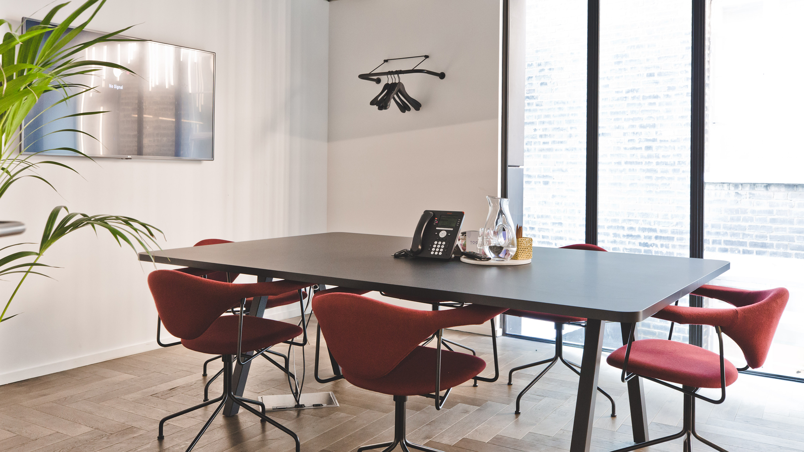 Small meeting room with dark rectangular table and red chairs and large windows at TOG building The Stanley Building London