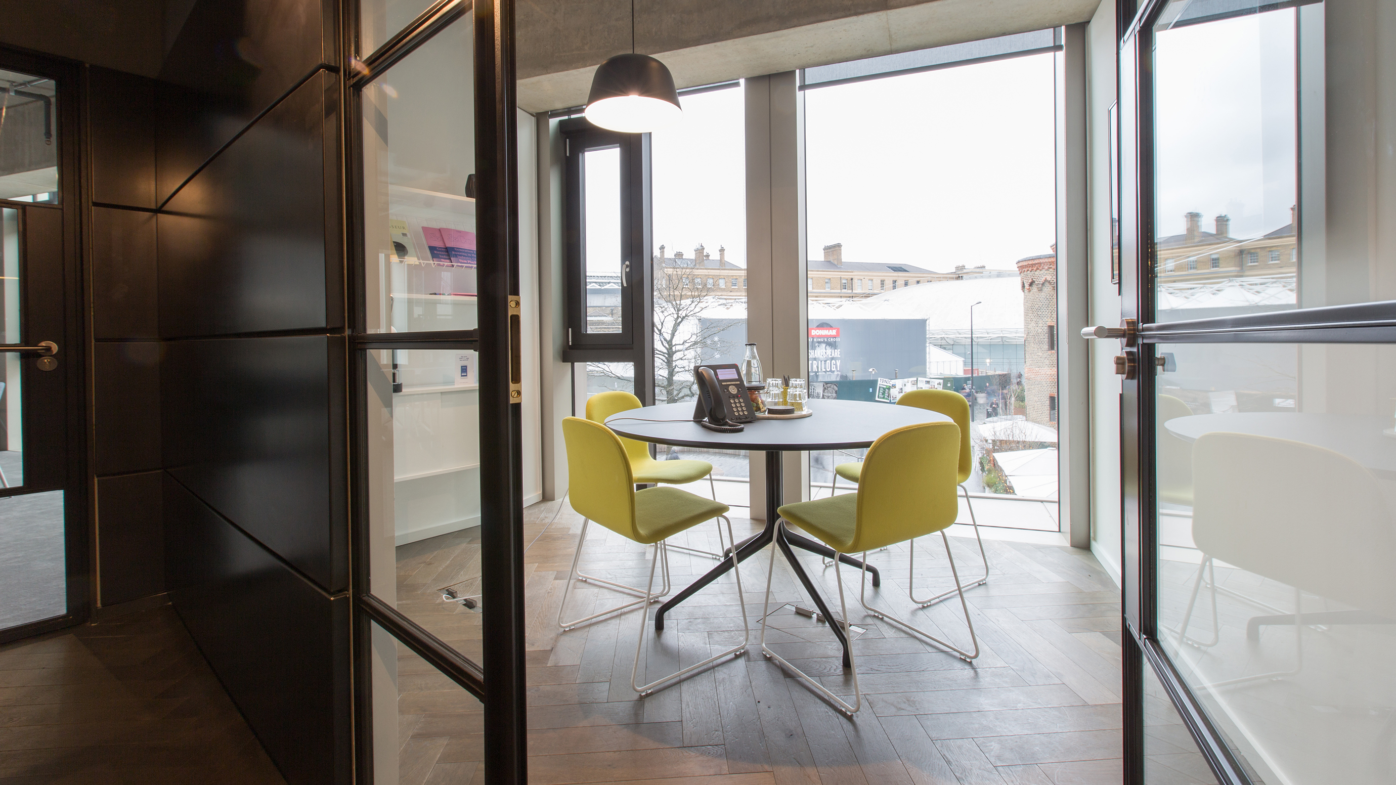 Small meeting room with round table and yellow chairs and large windows at TOG building The Stanley Building London