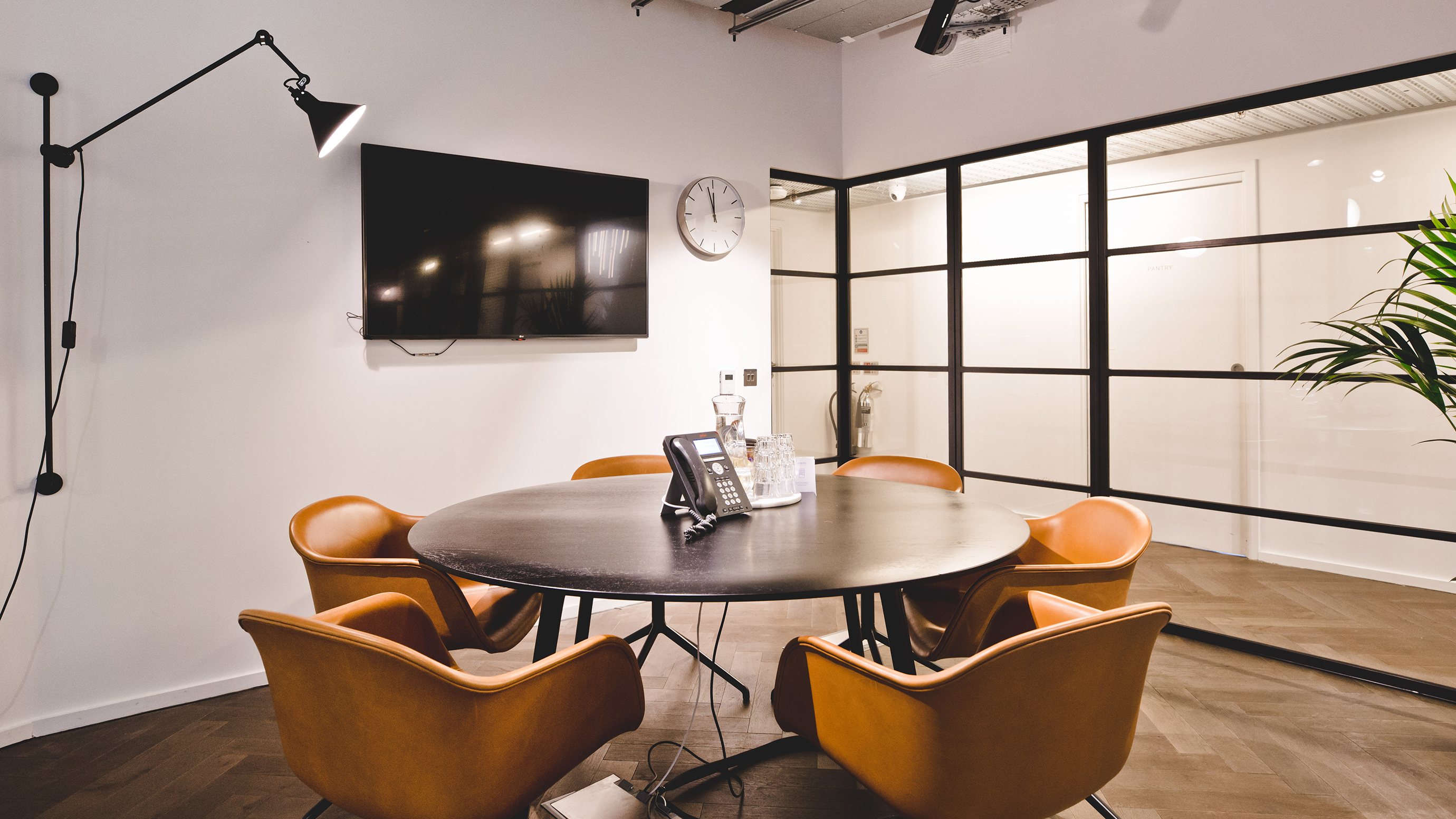 Small meeting room with dark round table and orange chairs and tv screen at TOG building The Stanley Building London