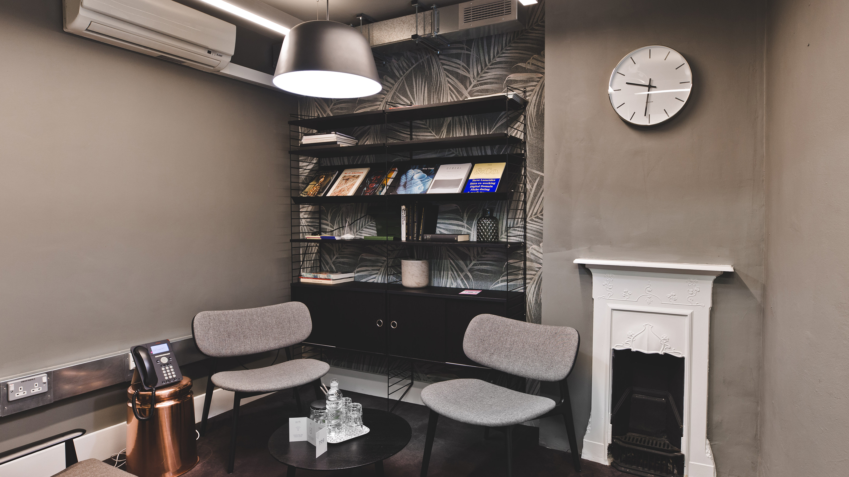 Small meeting room with grey chairs and fireplace and bookshelf at TOG building The Stanley Building London