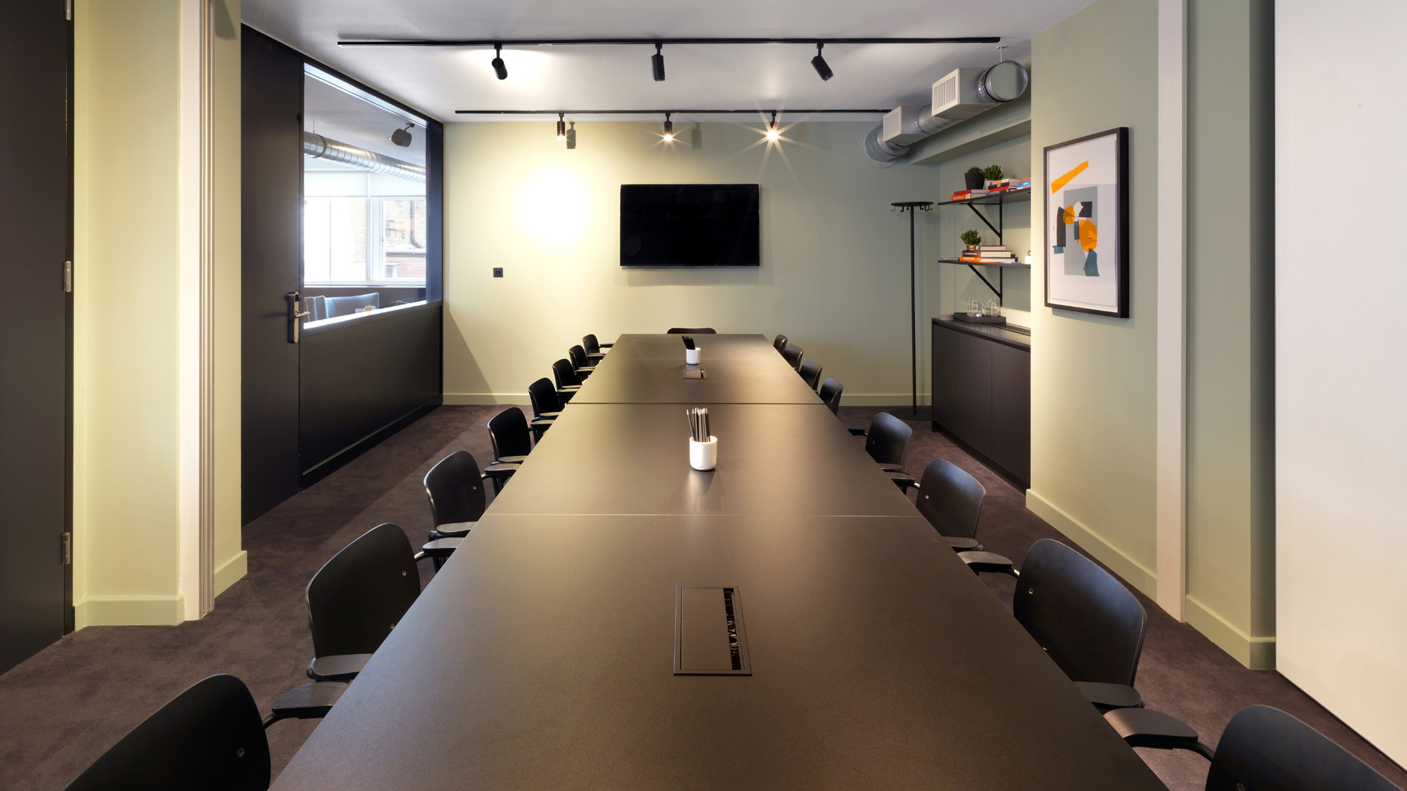 Long wooden meeting room table with black chairs and tv screen at TOG building 151 Wardour Street London