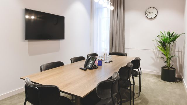 Medium meeting room with wooden table and black chairs and tv screen and plant at TOG building Belle House London