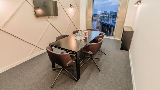 Small meeting room with dark rectangular table and brown chairs and tv screen at TOG building GridIron London