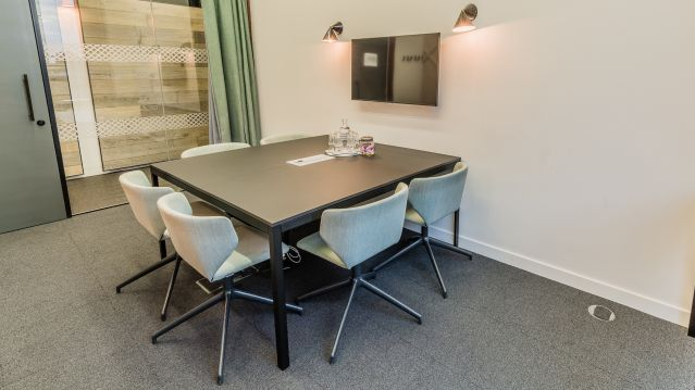 Small meeting room with black square wooden table and pale grey chairs and tv screen at TOG building GridIron London