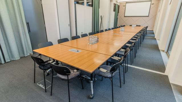 Large meeting room with long wooden table and dark chairs and screen at TOG building GridIron London