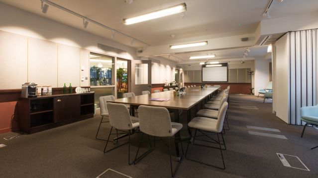 Large meeting room with dark long table and grey chairs at pink and white walls at TOG building The Bloomsbury Building London
