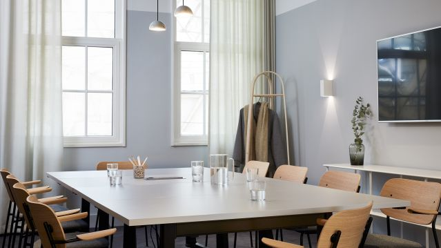Medium meeting room with pale table and wooden chairs and grey walls at TOG building Scott House London
