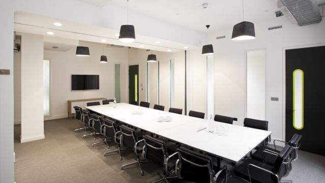 Large meeting room with long white table and dark chairs and tv screen at TOG building Stratford Place London