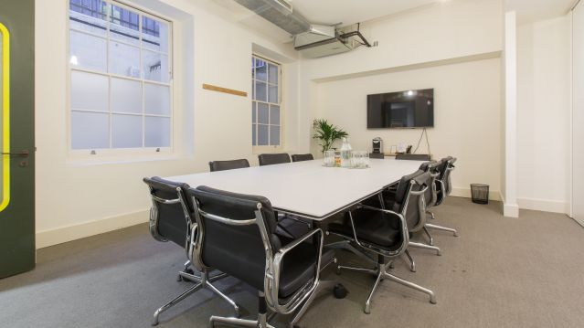 Medium meeting room with white table and dark chairs and white table at TOG building Stratford Place London