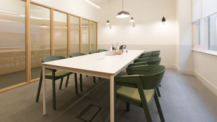 Medium meeting room with white rectangular table and green chairs at TOG building Lloyds Avenue London