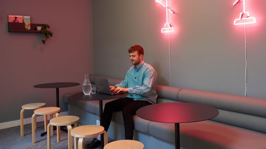 Lounge space at Whitechapel with neon light features, sofa and stool seating and individual tables.