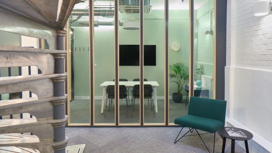 Stylish meeting room at Whitechapel with a glass feature wall, desk and chairs, and a large TV screen.