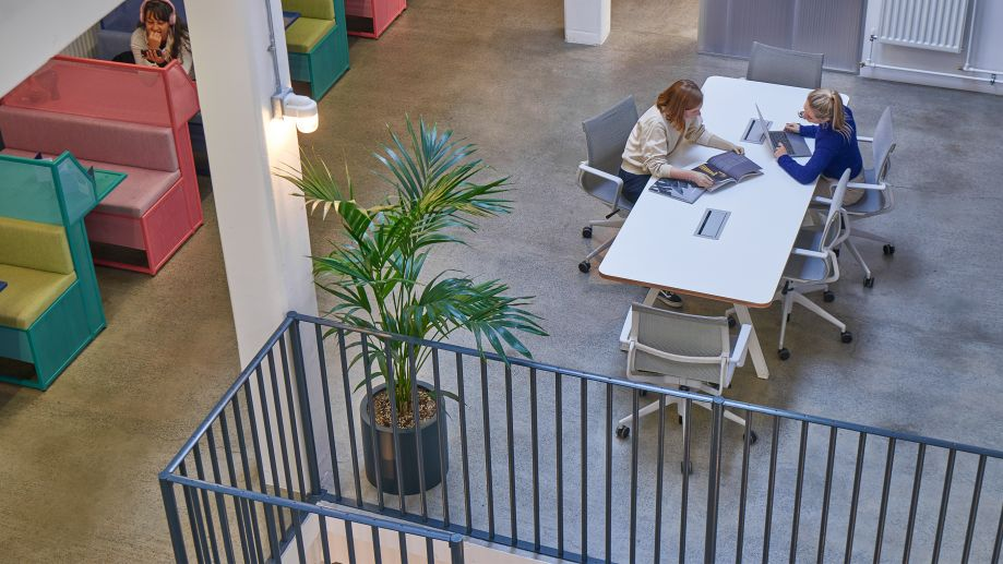 Coworking space at Whitechapel with breakout desks, colourful booths and leafy plants.