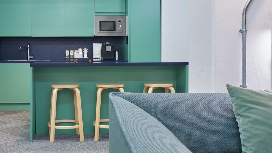 Communal kitchen area at Whitechapel painted in turquoise with a breakfast bar and stools and sofa seating.