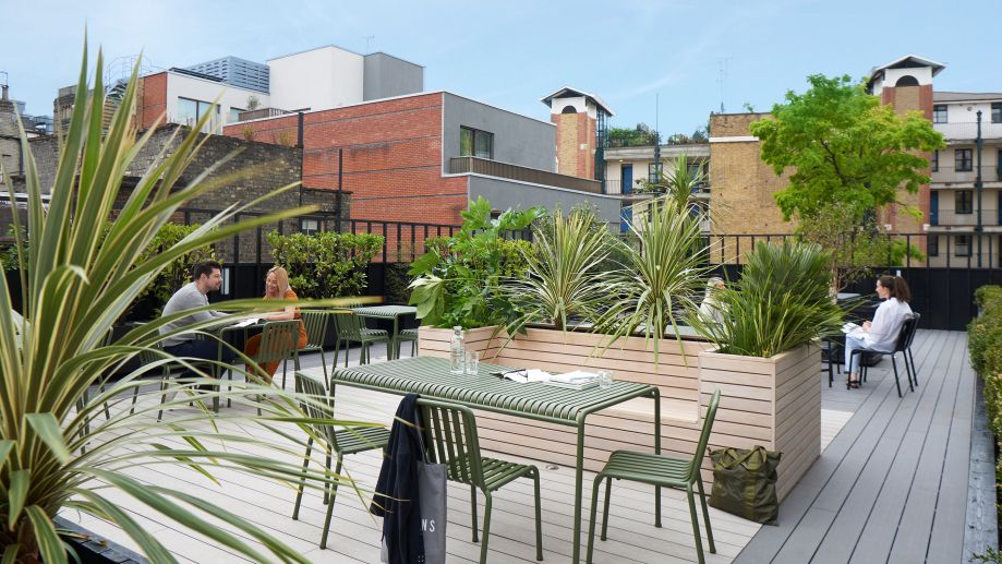 Leafy, open terrace at Orion House with wooden decking and seating, and green metal benches and tables.