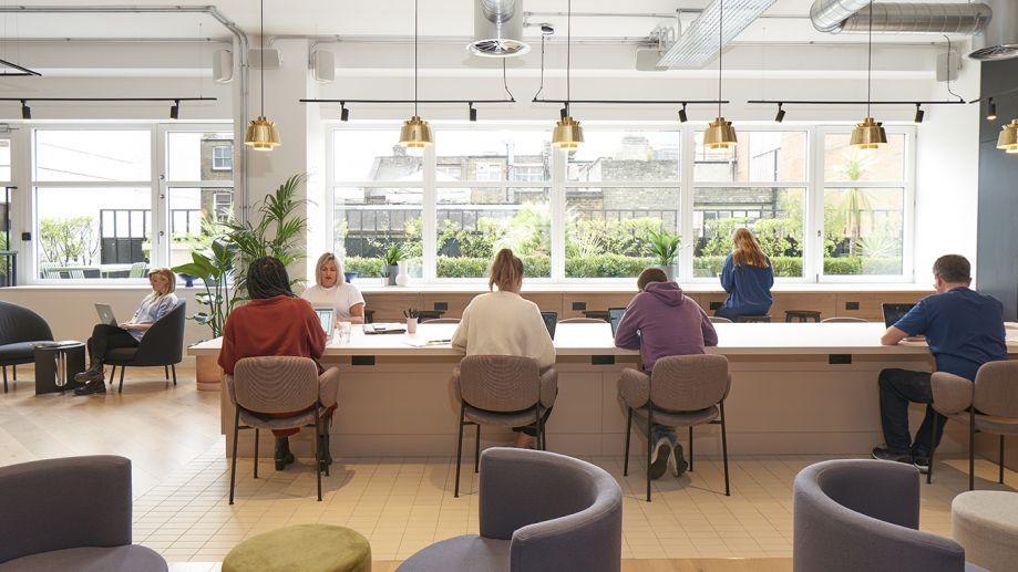 Coworking lounge at Orion House with a long central shared desk, counter seating and room-wide windows.
