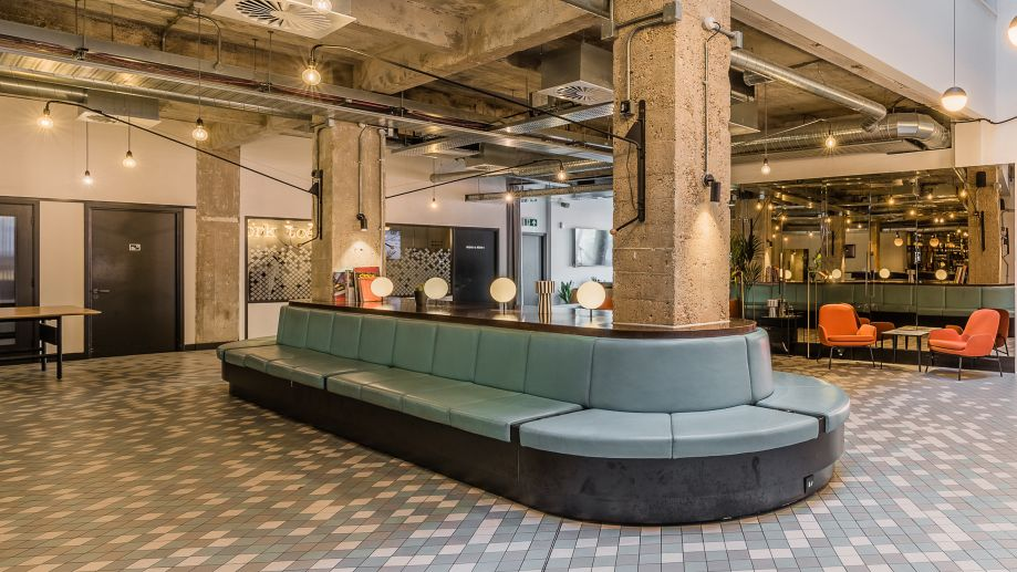 Cool event space at Albert House with industrial-style concrete walls and ceiling, tiled floors and a central seating area.